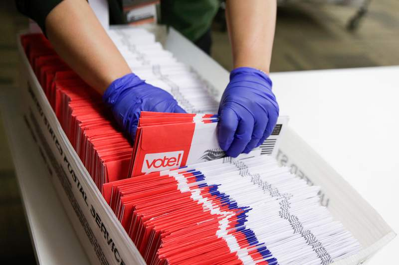 Election workers sort vote-by-mail ballots for the presidential primary at King County Elections in Renton, Washington on March 10, 2020. (Photo by Jason Redmond / AFP) (Photo by JASON REDMOND/AFP via Getty Images)