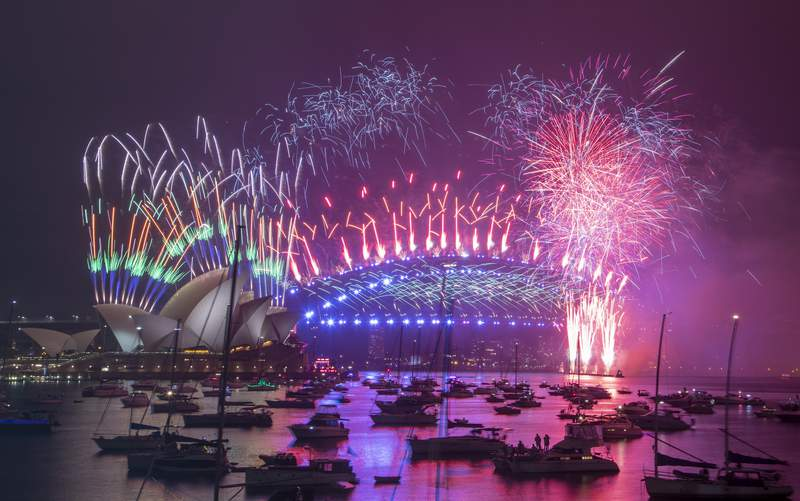 Fireworks explode over the Sydney Opera House and Harbour Bridge as New Year celebrations begin in Sydney, Australia, Friday, Jan. 1, 2021. One million people would usually crowd the Sydney Harbor to watch the annual fireworks that center on the Sydney Harbour Bridge. But this year authorities advised revelers to watch the fireworks on television as the two most populous states, New South Wales and Victoria battle to curb new COVID-19 outbreaks. (AP Photo/Mark Baker)