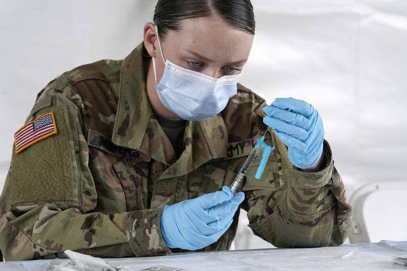 FILE - U.S. Army medic Kristen Rogers of Waxhaw, N.C. fills syringes with the Johnson & Johnson COVID-19 vaccine, Wednesday, March 3, 2021, in North Miami, Fla.  Critics in Florida say a doctors signature required for some people to get vaccinated is adding onerous barriers for some eligible residents, especially low-income or minority people who may not have health insurance or access to a primary care doctor.  (AP Photo/Marta Lavandier)