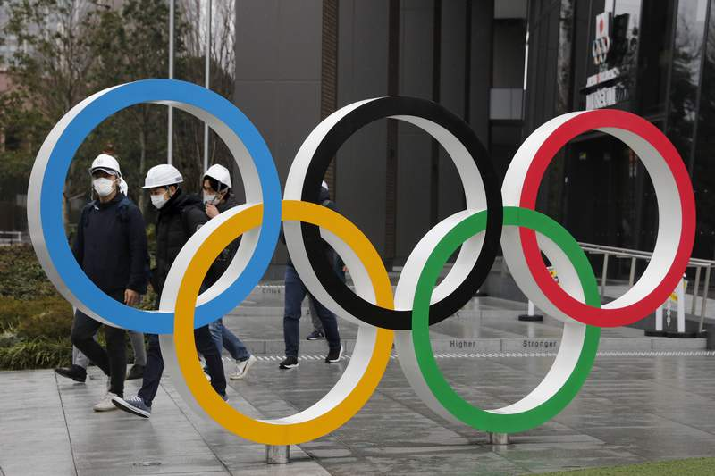 """FILE - In this March 4, 2020, file photo, people wearing masks walk past the Olympic rings near the New National Stadium in Tokyo. It's been 2 1/2 months since the Tokyo Olympics were postponed until next year because of the COVID-19 pandemic. So where do the games stand? So far, many ideas about how the Olympic can take place are being floated by the International Olympic Committee, Japanese officials and politicians, and in unsourced Japanese newspaper articles coming from local organizers and politicians. The focus is on soaring costs, fans, or no fans, possible quarantines for athletes, and cutting back to only the essentials."""" (AP Photo/Jae C. Hong, File)"""