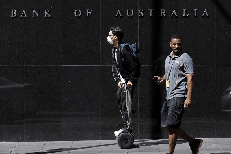 FILE - In this March 19, 2020, file photo, a man wearing a mask, left, rides a personal transporter past the Reserve Bank of Australia in Sydney. The coronavirus pandemic pushed Australias economy into recession for the first time in 29 years in the first quarter of the year 2022, and the situation is expected to get worse.  (AP Photo/Rick Rycroft, File)