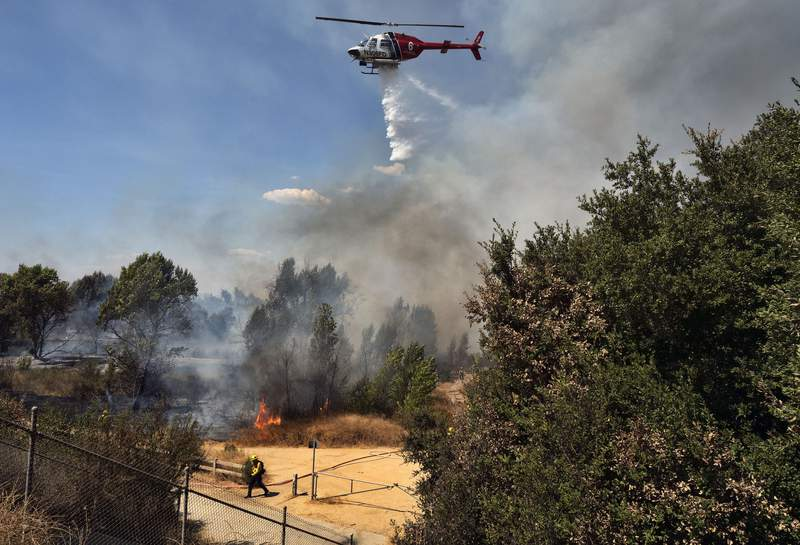 A Los Angeles Fire Department helicopter makes a water drop over a brush fire in the Sepulveda Basin in the Sherman Oaks area of Los Angeles, Sunday, Sept. 6, 2020. In Southern California, crews scrambled to douse several fires that popped up. The largest was a blaze in the foothills of Yucaipa east of Los Angeles that prompted evacuation orders for eastern portions of the city of 54,000 along with several mountain communities. (AP Photo/Richard Vogel)