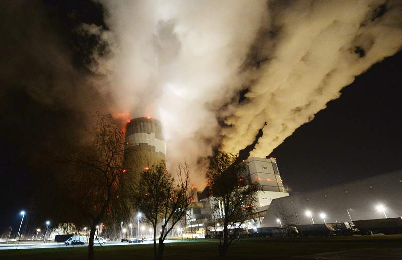 FILE - In this Wednesday Nov. 28, 2018 file photo, clouds of smoke over Europe's largest lignite power plant in Betchatow, central Poland. Energy experts were working to restore full operations at Polands biggest power plant, the lignite-fueled Belchatow, after an energy network failure switched off 10 of the plants 11 units. Poland needed energy imports from Germany, Sweden, the Czech Republic and Slovakia to fill in for the suddenly missing power. (AP Photo/Czarek Sokolowski, File)