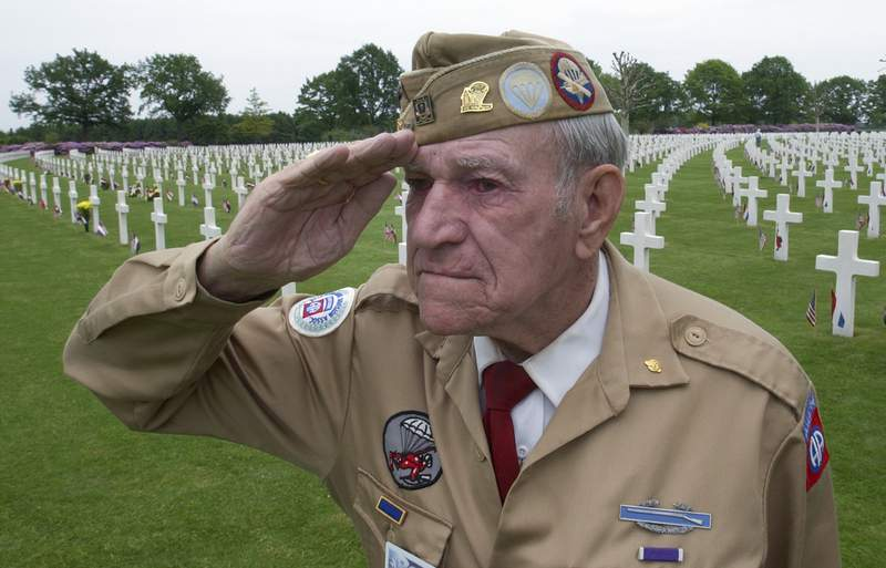 FILE- In this Sunday, May 30, 2004, file image, World War II veteran Corporal technician Harry Hudec of Cleveland, Ohio, salutes as the last post is played as he attends the 60-year commemoration service ahead of Memorial Day at the Netherlands American Cemetery in Margraten, southern Netherlands. With the help of volunteers in the Netherlands, Belgium and the United States scouring newspaper archives and other sources, the Faces of Margraten project of Dutch historian Sebastiaan Vonk has so far uncovered photos of more than 7,500 of the U.S servicemen and women buried or commemorated at Margraten. They were due to be displayed next to graves in Margraten this week as Europe commemorates the 75th anniversary of the end of World War II, but the event was cancelled due to COVID-19 coronavirus related measures. (AP Photo/Peter Dejong)