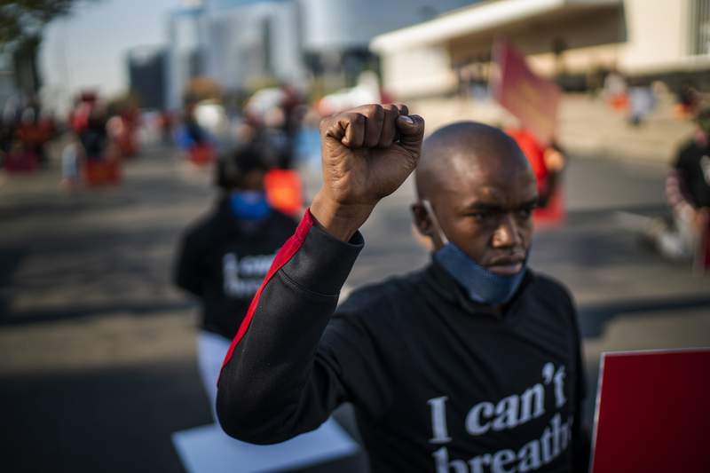 Demonstrators take a knee for eight minutes and 46 seconds in front of the U.S. Consulate General in Johannesburg, South Africa, Monday June 8, 2020. The protest in support of Black Lives Matter was called by the Economic Freedom Fighters (EFF) party in response to the recent killing of George Floyd by police officers in Minneapolis, USA, that has led to protests in many countries and across the US. (AP Photo/Jerome Delay)