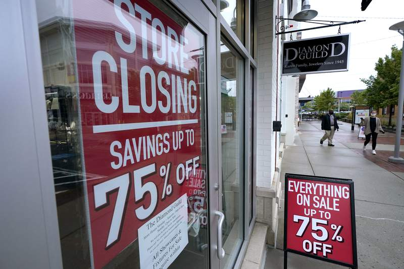 FILE - In this Sept. 2, 2020 file photo, pedestrians walk past a business storefront with store closing and sale signs in Dedham, Mass.  The U.S. economy plunged at a record rate in the spring but is poised to break a record for an increase in the just-ending July-September quarter. The Commerce Department reported Wednesday, Sept. 30, that the gross domestic product, the economys total output of goods and services, fell at a rate of 31.4% in the April-June quarter, only slightly changed from the 31.7% drop estimated one month ago.  (AP Photo/Steven Senne)