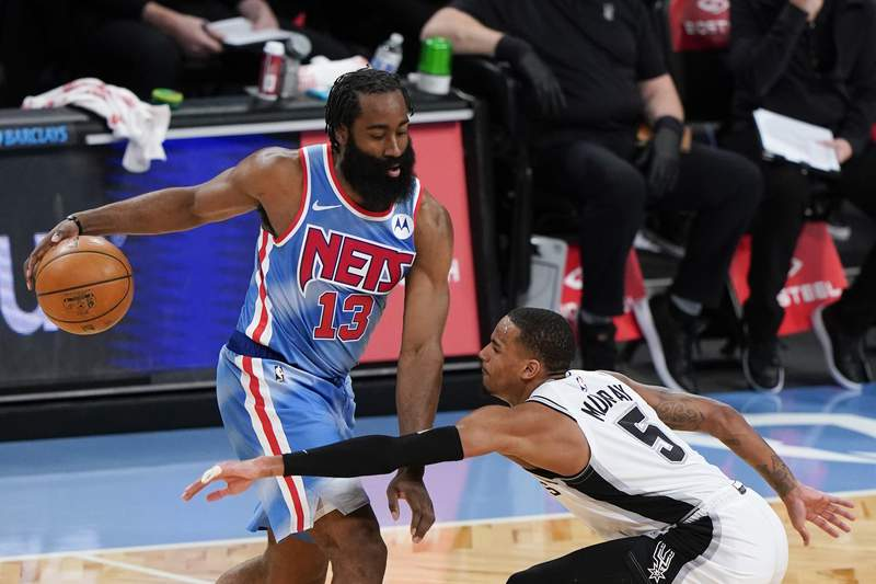 San Antonio Spurs' Dejounte Murray (5) defends Brooklyn Nets' James Harden (13) during the first half of an NBA basketball game Wednesday, May 12, 2021, in New York. (AP Photo/Frank Franklin II)