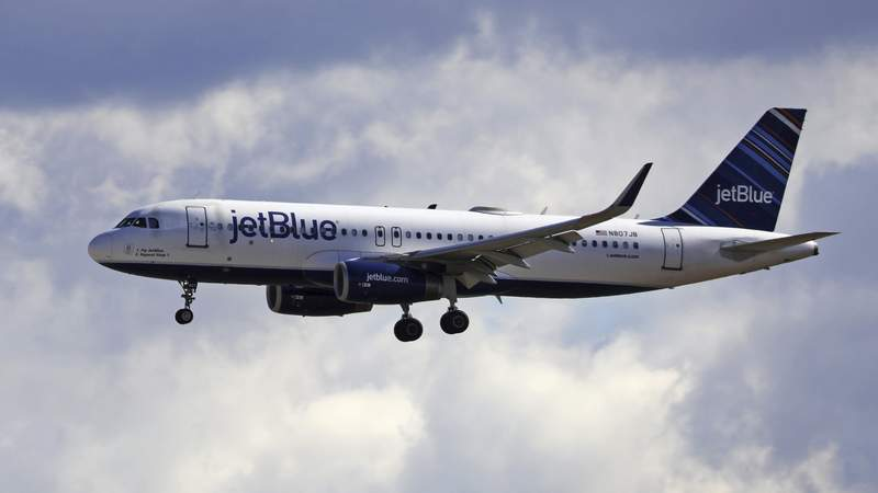 FILE - In this Oct. 18, 2019, file photo a JetBlue Airways flight flies in to Salt Lake City International Airport in Salt Lake City.   JetBlue says it plans to increase the number of seats it will fill on planes starting in December. That makes JetBlue the latest airline to retreat from blocking middle seats to give passengers more space because of the pandemic. (AP Photo/Rick Bowmer, File)