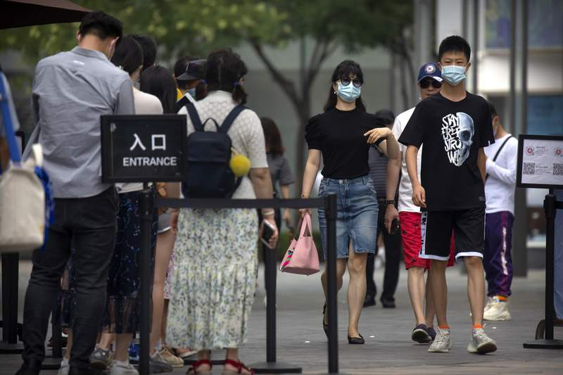 FILE: People wearing face masks to protect against the new coronavirus walk past a line of people waiting to show the results of a smartphone health check app before they can enter an outdoor shopping mall in Beijing, Saturday, July 4, 2020. China reported a single new case of coronavirus in Beijing on Saturday, plus a few more cases elsewhere believed to have come from abroad. (AP Photo/Mark Schiefelbein)