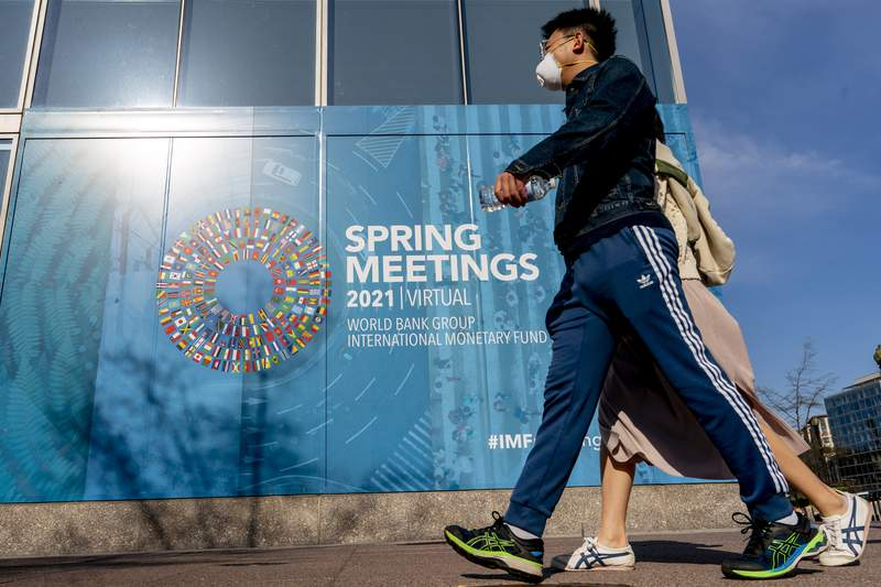 A poster is displayed on the International Monetary Fund building, Monday, April 5, 2021, in Washington. The IMF and the World Bank open their virtual spring meetings. (AP Photo/Andrew Harnik)