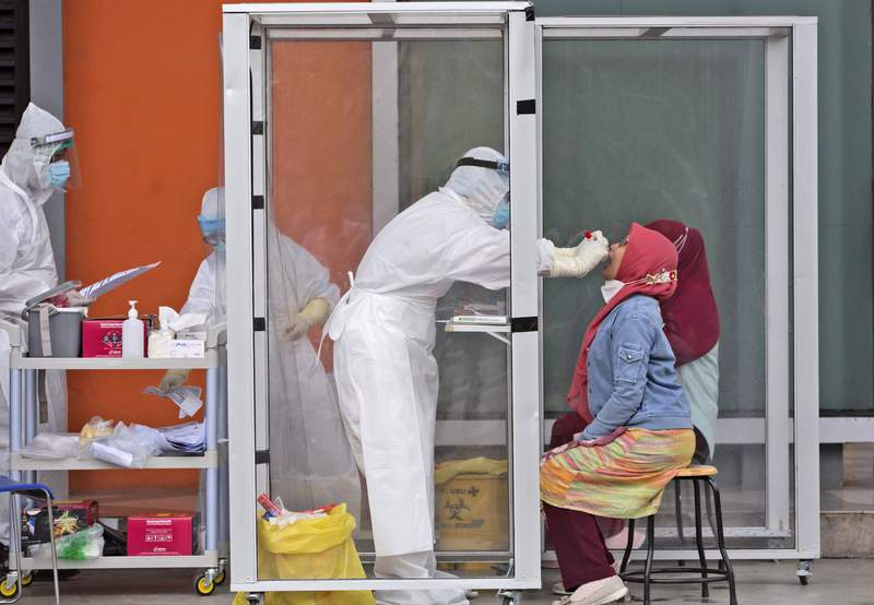 A medical worker collects nasal swab samples from a woman during a mass test for the new coronavirus at North Sumatra University (USU) in Medan, North Sumatra, Indonesia, Tuesday, July 14, 2020. The mass test was held after the rector of the university along with one of his deputies and a member of the board of trustees were tested positive for COVID-19. (AP Photo/Binsar Bakkara)