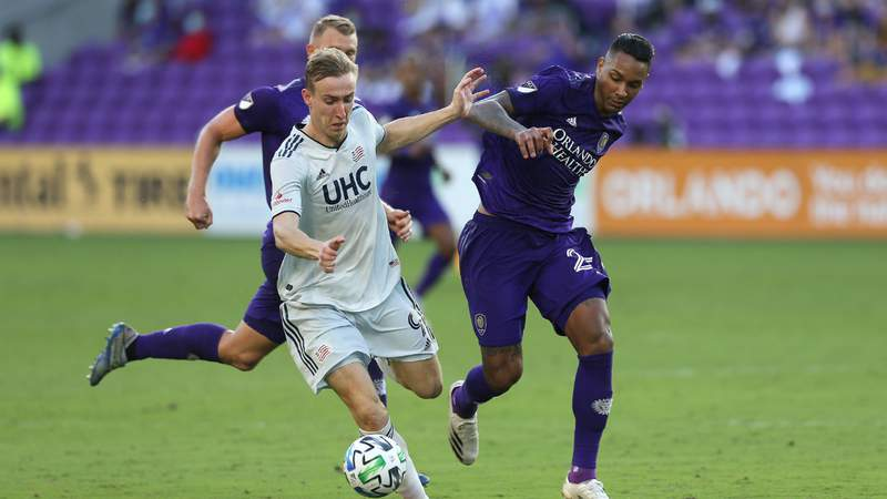 Adam Buksa #9 of New England Revolution drives past Antonio Carlos #25 of Orlando City SC during the MLS Eastern Conference Semifinal playoff match at Exploria Stadium. Photo by Alex Menendez