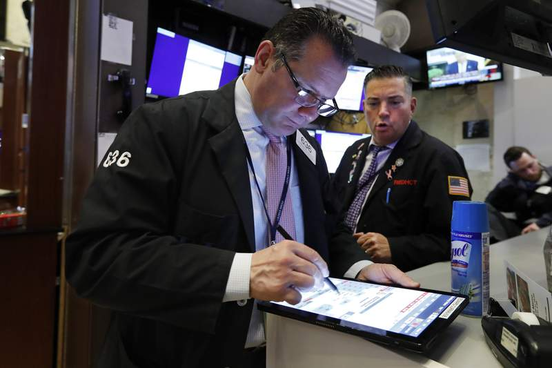 Traders Edward Curran, left, and Jonathan Mueller work on the floor of the New York Stock Exchange, Thursday, March 12, 2020. The deepening coronavirus crisis is sending stocks into another alarming slide on Wall Street, triggering a brief, automatic shutdown in trading for the second time this week. (AP Photo/Richard Drew)