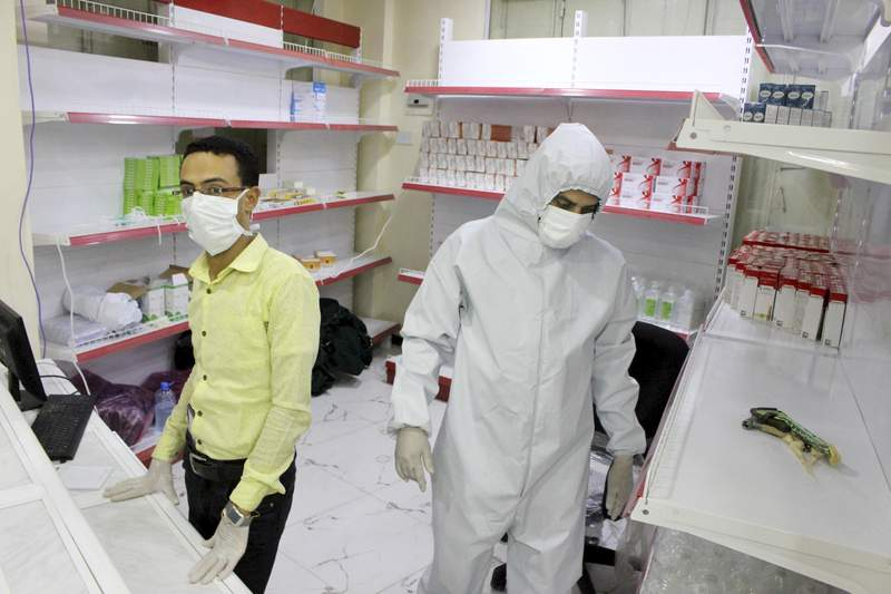 FILE - In this May 12, 2020 file, photo, Yemeni medical workers wearing masks and protective gear stand at the entrance of a hospital in Aden, Yemen. The international aid group Doctors Without Borders has reported a spike of deaths and infections from coronavirus, including health workers at a facility it runs in Aden. Residents of Aden had previously said several hospitals shut their doors as medical staffers feared contracting the virus while lacking protective equipment. (AP Photo/Wail al-Qubaty, File)