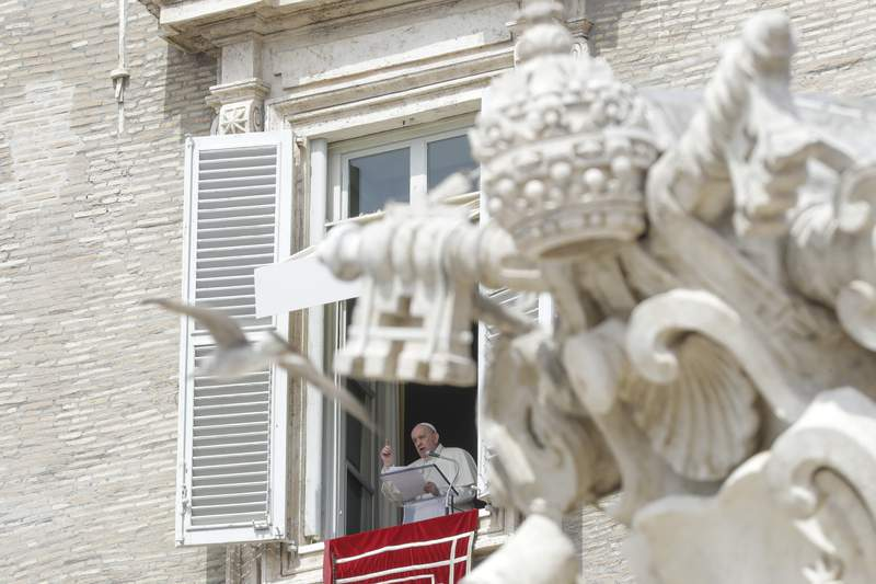 Pope Francis delivers his blessing as he recites the Regina Caeli noon prayer from the window of his studio overlooking St.Peter's Square, at the Vatican, Sunday, April 18, 2021. Pope Francis said he is happy to be back greeting the faithful in St. Peters Square faithful for his traditional Sunday noon blessing after weeks of lockdown measures.  (AP Photo/Andrew Medichini)