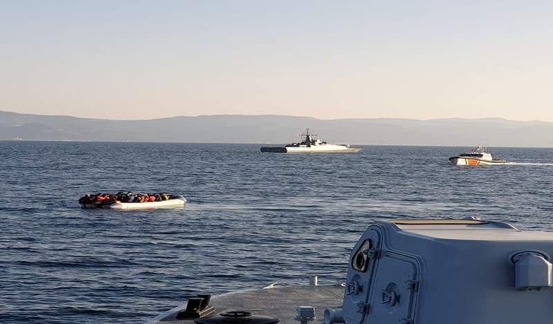 In this photo provided by the Hellenic Coast Guard and taken from a vessel shows a dinghy with migrants, left, with Turkish ships in the background, in the narrow stretch of water between the eastern Greek island of Lesbos and the Turkish coast on Friday, April 2, 2021. Greece is reporting a series of incidents with the Turkish coast guard in the narrow stretch of water between the eastern Greek island of Lesbos and the Turkish coast, at a time of generally testy relations between the two neighbors and NATO allies. The Greek coast guard said three incidents occurred Friday morning northeast of Lesbos, an island on the main migrant smuggling route from Turkey to Greece. It said two involved Turkish coast guard vessels escorting or pushing dinghies carrying migrants toward Greek territorial waters. There was no immediate reaction from Turkish authorities. Turkey and Greece have long traded accusations over the migration issue. (Hellenic Coast Guard via AP)