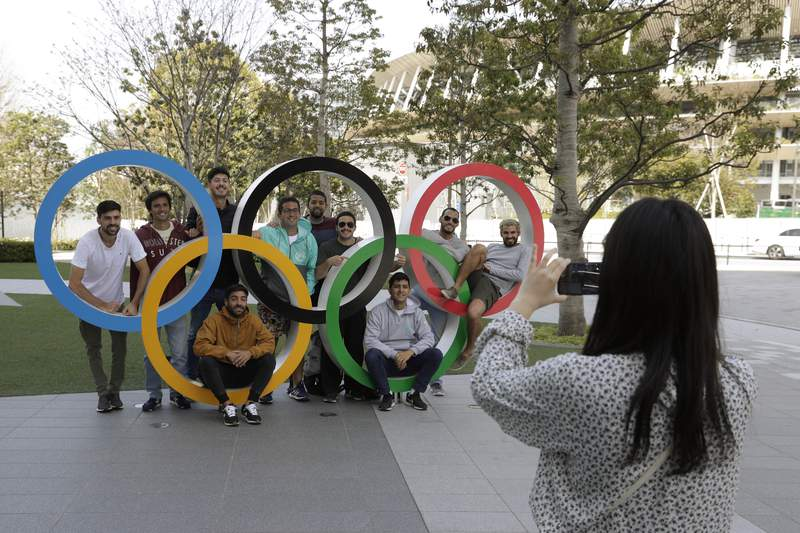 A group of students from Uruguay pose for a souvenir picture on the Olympic Rings set outside the Olympic Stadium in Tokyo, Saturday, March 21, 2020. The Olympic flame from Greece arrived in Japan Friday, even as the opening of the the Tokyo Games in four months is in doubt with more voices suggesting the games should to be postponed or canceled because of the worldwide virus pandemic. (AP Photo/Gregorio Borgia)