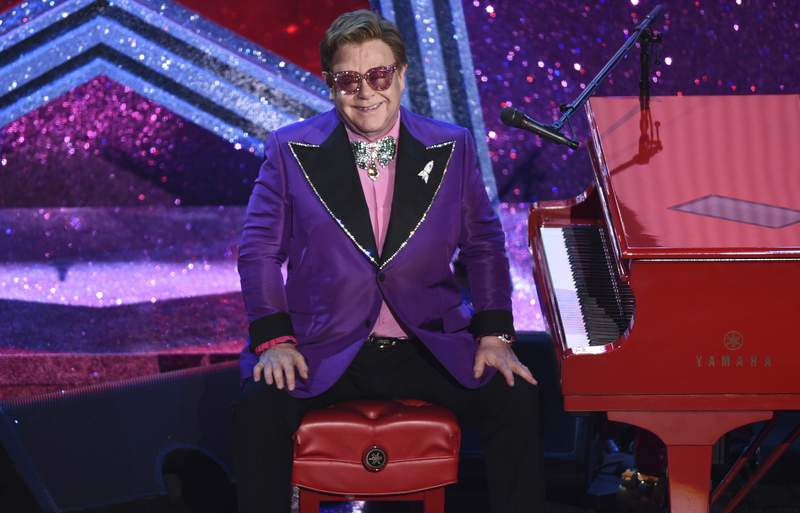 """FILE - In this Sunday, Feb. 9, 2020, file photo, Elton John appears after performing his nominated song, """"(I'm Gonna) Love Me Again,"""" at the Oscars in Los Angeles. Attending Elton Johns long-running Oscar-night party has always been one of the hardest tickets to get. Now you can go  if you have $20. The Elton John AIDS Foundation is inviting everyone to a hour-long, virtual pre-show Oscar party special hosted by Neil Patrick Harris and with a performance by Dua Lipa. Tickets for the April 25 event are $19.99 and are available via Ticketmaster. Proceeds will go to young people at risk and living with HIV all over the world. (AP Photo/Chris Pizzello, File)"""