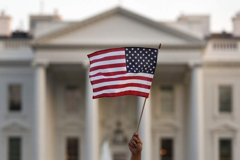 """FILE - In this Sept. 2017 file photo, a flag is waved during an immigration rally outside the White House, in Washington.  The Trump administration says it'll allow migrants from six countries to extend their legal U.S. residency under a temporary status for nine months while courts consider its effort to end the program. President Donald Trump has long sought to terminate the program, which allows migrants from countries devastated by war or natural disaster to legally live in the U.S. President-elect Joe Biden has promised an immediate review"""" of it and said hell pursue legislation for longtime residents to remain and seek U.S. citizenship. The Department of Homeland Security announced the extension Wednesday.  (AP Photo/Carolyn Kaster)"""