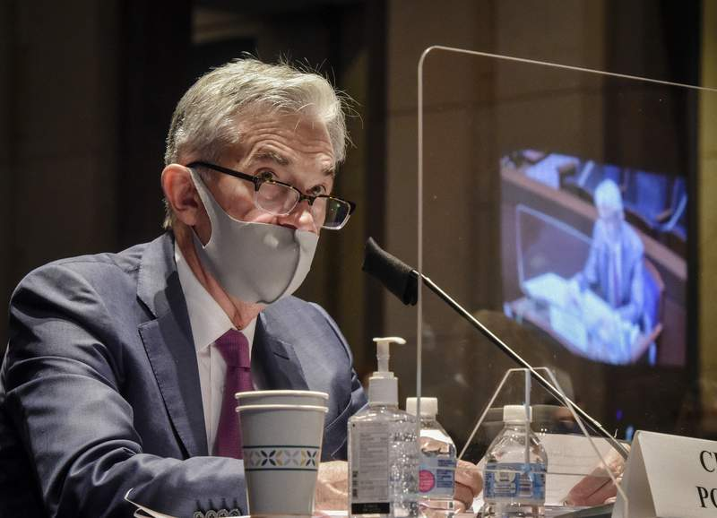 FILE - In this June 30, 2020, file photo Federal Reserve Board Chairman Jerome Powell, reflected in the sneeze guard set up between himself and members of the House Committee on Financial Services, speaks during a hearing on oversight of the Treasury Department and Federal Reserve pandemic response on Capitol Hill in Washington. With the economy still in the pandemics grip, the Federal Reserve is facing a decision on whether to stretch an emergency lending program in a way that could bring more risk for the government and taxpayers. Lawmakers are pressing the central bank to deliver more aid to struggling small and mid-sized businesses. (Bill O'Leary/The Washington Post via AP, Pool)