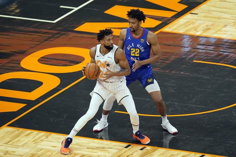 Orlando Magic center Khem Birch, left, looks for a way past Denver Nuggets forward Zeke Nnaji (22) during the first half of an NBA basketball game, Tuesday, March 23, 2021, in Orlando, Fla. (AP Photo/John Raoux)
