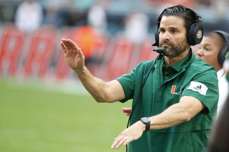 FILE - In this Saturday, Nov. 9, 2019 file photo, Miami head coach Manny Diaz calls out a play during the first half of an NCAA college football game against Louisville in Miami Gardens, Fla. Miami coach Manny Diaz told The Associated Press on Monday, Feb. 3, 2020 that he believes the Hurricanes are already better than they were when last season's 6-7 debacle ended. Diaz says the Hurricanes have improved their roster and their coaching staff, both by additions and subtractions. He also drew a parallel to the culture that the Miami Heat have stuck with in their bounceback season this year.  (AP Photo/Wilfredo Lee, File)
