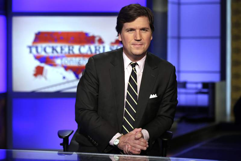 """FILE - In this March 2, 2017, file photo, Tucker Carlson, host of """"Tucker Carlson Tonight,"""" poses for photos in a Fox News Channel studio in New York. Fox News announced that starting next week, it will make reruns of prime-time television shows hosted by Tucker Carlson, Sean Hannity and Laura Ingraham available to watch 24 hours a day, seven days a week. Those programs will be streamed starting the next day to subscribers of the Fox Nation service. (AP Photo/Richard Drew, File)"""