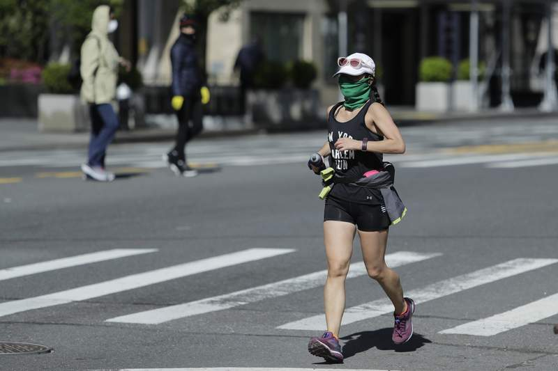 A woman wearing a protective mask runs along Central Park South Saturday, May 2, 2020, in New York. New York City police dispatched 1,000 officers this weekend to enforce social distancing due to coronavirus concerns, as warmer weather tempted New Yorkers to come out of quarantine. Officers set out on foot, bicycles and cars to break up crowds and remind everyone of public health restrictions requiring they keep 6 feet away from others.(AP Photo/Frank Franklin II)