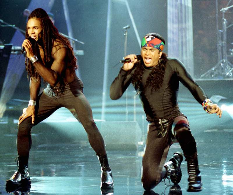 FILE - In this Oct. 26, 1992 file photo, Fabrice Morvan, left, and Rob Pilatus of Milli Vanilli perform during the taping of the Arsenio Hall Show in Los Angeles. John Davis, one of the real singers behind the lip-synching duo, died of the coronavirus this week. The South Carolina native was 66. Davis was credited as a backup singer on the pop duo's albums. (AP Photo/Craig Fujii, File)