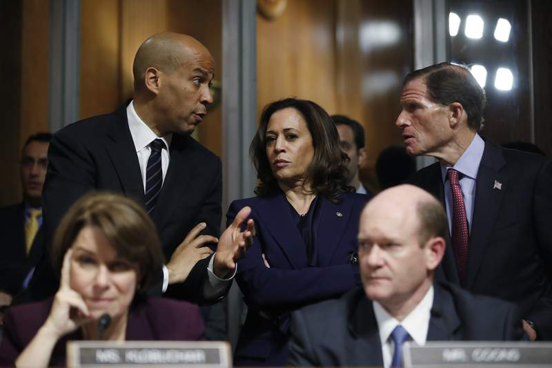 FILE - In this Sept. 28, 2018, file photo Senate Judiciary Committee members Sen. Cory Booker, D.-N.J., top left, Sen. Kamala Harris, D-Calif., and Sen Richard Blumenthal, D-Conn., right, talk as Sen. Jeff Flake, R-Ariz., discusses his concerns before the committee on Capitol Hill in Washington. Sen. Amy Klobuchar, D-Minn. and Sen. Chris Coons, D-Del., are seated. (AP Photo/Pablo Martinez Monsivais, File)