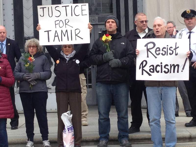 """In this 2016 photo, Martin Gugino, right, holds a sign reading """"Resist Racism,"""" in Washington, D.C., as part of a protest over the 2014 killing of 12 year-old African American Tamir Rice in Cleveland.  Gugino and others demanded murder charges against police officers for the killing. (Mark Colville via AP)"""