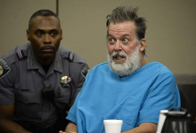FILE - In this Dec. 9, 2015, file photo, Robert Dear talks to Judge Gilbert Martinez during a court appearance in Colorado Springs, Colo. Federal prosecutors said Wednesday, Dec. 2, 2020, they would not seek the death penalty against Dear, accused of killing three people and injuring nine others at a Planned Parenthood clinic in Colorado in 2015. Prosecutors have repeatedly deemed incompetent to stand trial. Dear, however, has insisted he is competent.  (Andy Cross/The Denver Post via AP, Pool, File)