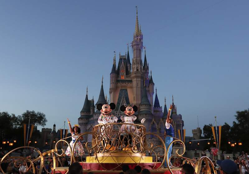 FILE - In this Jan. 15, 2020, file photo, Mickey and Minnie Mouse perform during a parade as they pass by the Cinderella Castle at the Magic Kingdom theme park at Walt Disney World in Lake Buena Vista, Fla. Florida tourism officials say cases of the new coronavirus are having little visible impact on the state's biggest industry so far. Disney officials said in a statement that extra hand sanitizers were being placed throughout its four parks and more than two dozen hotels. (AP Photo/John Raoux, File)
