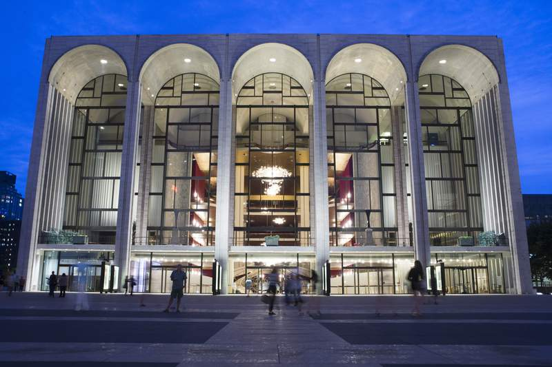 FILE - In this Aug. 1, 2014, file photo, pedestrians make their way in front of the Metropolitan Opera house at New York's Lincoln Center. The Metropolitan Opera has canceled performances and rehearsals through March 31 because of the coronavirus. The move was announced Thursday, March 12, 2020, one day after U.S. President Donald Trump announced a suspension of travel to the U.S. from Europe for 30 days starting Friday. For most people, the new coronavirus causes only mild or moderate symptoms. For some it can cause more severe illness. (AP Photo/John Minchillo, File)