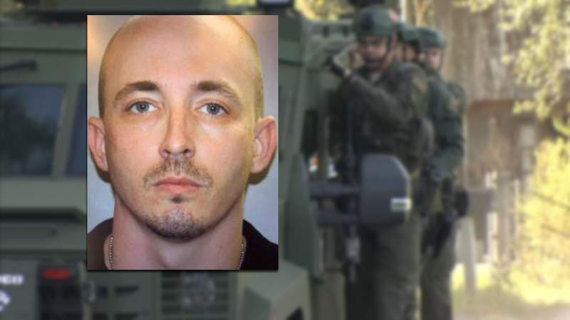 SWAT team members were going door to door on Saturday as the search continued for Patrick McDowell, who is accused of shooting a Nassau County deputy during a traffic stop on Friday morning.