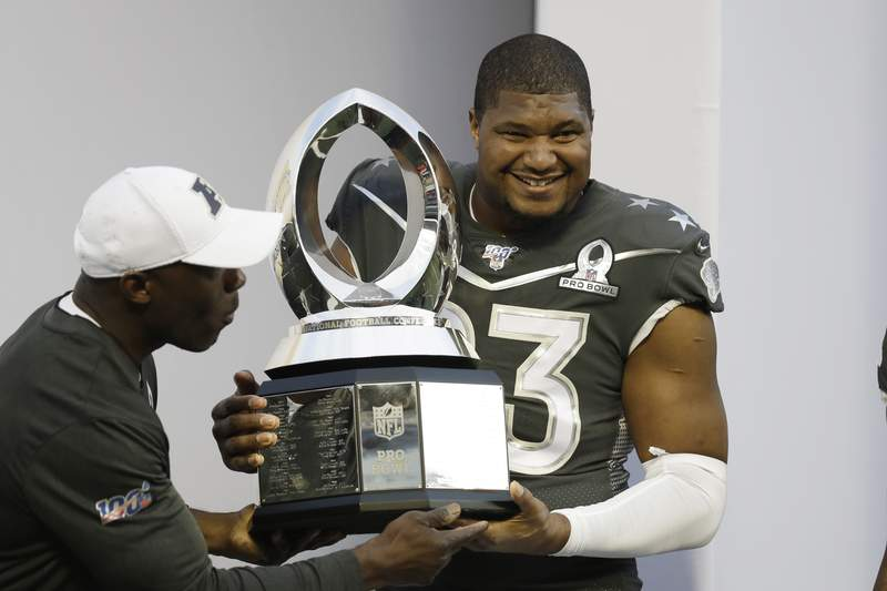 AFC defensive end Calais Campbell, of the Jacksonville Jaguars, (93) holds the Pro Bowl trophy after the NFL Pro Bowl football game, Sunday, Jan. 26, 2020, in Orlando, Fla. The AFC defeated the NFC 38-33. Campbell won the MVP defensive player of the game. (AP Photo/Chris O'Meara)