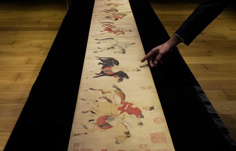 """A Sotheby's employee presents the Chinese scroll, """"Five Drunken Princes Returning on Horseback"""" from the period of Chinese Yuan Dynasty, by Ren Renfa during a media preview for the Sotheby's in Hong Kong on Wednesday, Sept. 23, 2020. The 700-year-old painted scroll has been sold for $41.8 million at an auction in Hong Kong. (AP Photo/Vincent Yu, File)"""