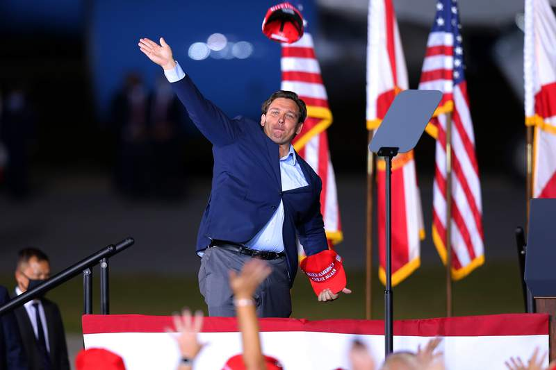 Florida Gov. Ron DeSantis throws a hat to supporters during a rally for President Donald Trump on Oct. 23, 2020 in Pensacola, Florida.