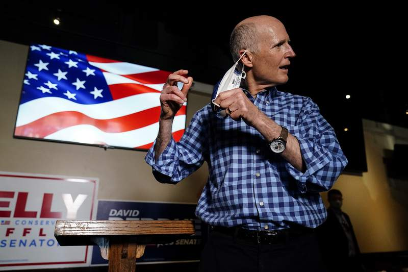 Sen. Rick Scott, R-Fla., takes off his mask before he speaks to the media after a campaign rally for Republican candidates for U.S. Senate Sen. Kelly Loeffler and Sen. David Perdue on Friday, Nov. 13, 2020, in Cumming, Ga. (AP Photo/Brynn Anderson)