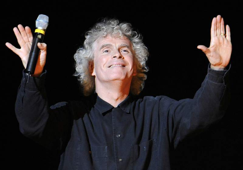 """FILE - In this March 27, 2010 file photo, conductor Sir Simon Rattle gestures prior to a dress rehearsal for Richard Wagner's opera """"Goetterdaemmerung"""" which was part of the Salzburg Easter Festival in Salzburg, Austria. Simon Rattle is set to leave his job as musical director at the London Symphony Orchestra to lead the Munich-based Bavarian Radio Symphony Orchestra. The the two organizations said Monday, Jan. 11, 2021 that the acclaimed conductor will become the German orchestras chief conductor in 2023. (AP Photo/Kerstin Joensson, File)"""
