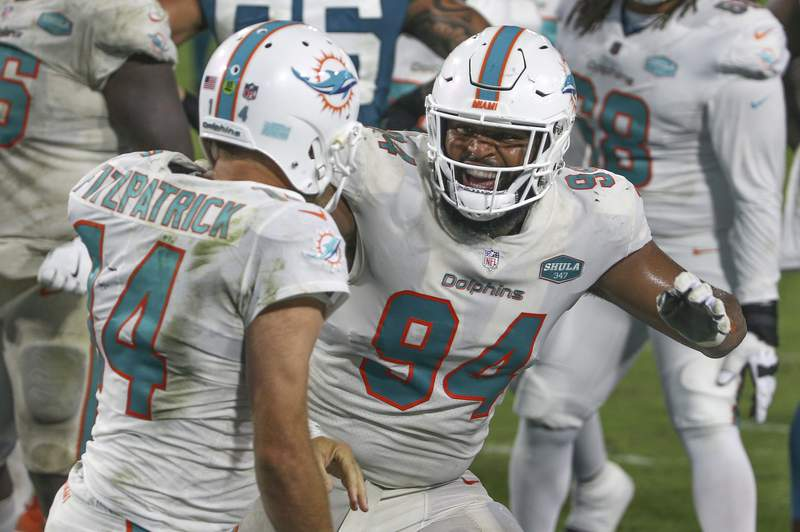 Miami Dolphins tackle Christian Wilkins (94) celebrates with quarterback Ryan Fitzpatrick (14) after Fitzpatrick scored a touchdown on a 1-yard run against the Jacksonville Jaguars during the second half of an NFL football game, Thursday, Sept. 24, 2020, in Jacksonville, Fla. (AP Photo/Stephen B. Morton)