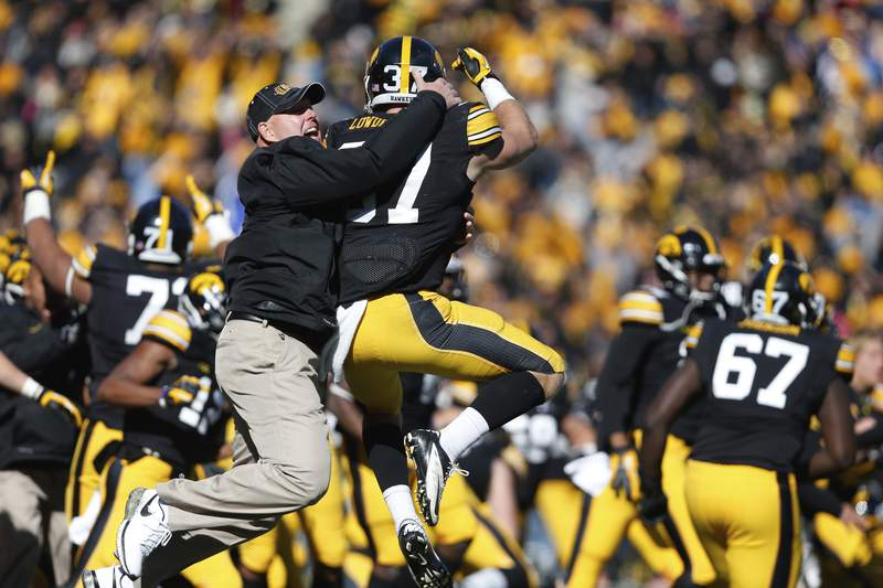 "FILE - In this Oct. 26, 2013, file photo, Iowa strength and conditioning coach Chris Doyle, front left, celebrates with defensive back John Lowdermilk (37) following their win in overtime against Northwestern in an NCAA college football game  in Iowa City, Iowa. Iowa football strength and conditioning coach Doyle has been placed on administrative leave after several black former players posted on social media about what they described as systemic racism in the program.  Head coach Kirk Ferentz made the announcement Saturday, June 6, 2020, calling it ""a defining moment for Iowa's football program in a video posted on the team's Twitter account. (AP Photo/Brian Ray, File )"
