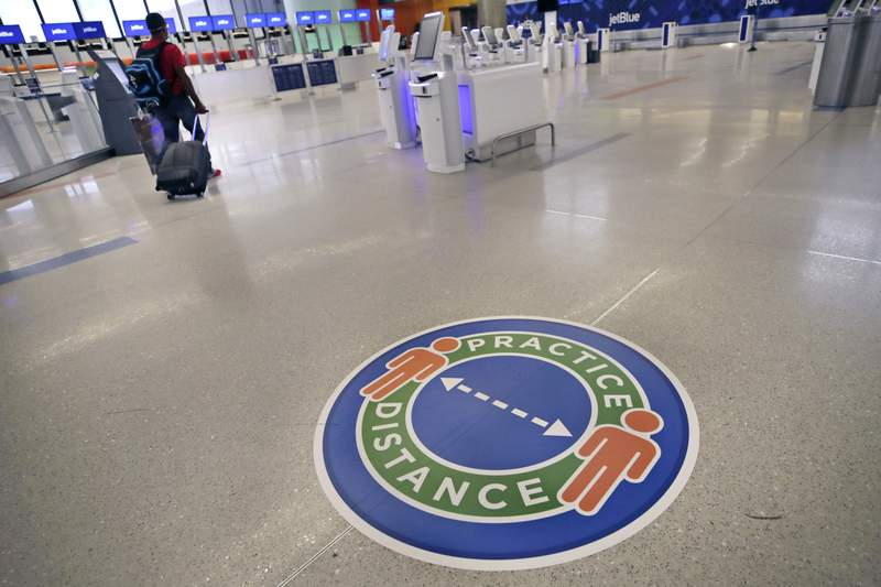A traveler passes a sign recommending practicing social distancing, to limit spread of the coronavirus outbreak, at the nearly passenger-less JetBlue terminal at Logan Airport in Boston, Friday, May 29, 2020. (AP Photo/Charles Krupa)