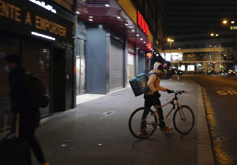 FILE - In this file photo dated Monday Feb. 15, 2021, a Deliveroo food delivery worker pushes his bike in front of restaurant in Paris.  Shares in the app-based meal delivery service Deliveroo tumbled by as much as a third in their U.K. stock market debut on Wednesday March 31, 2021.  (AP Photo/Francois Mori, FILE)