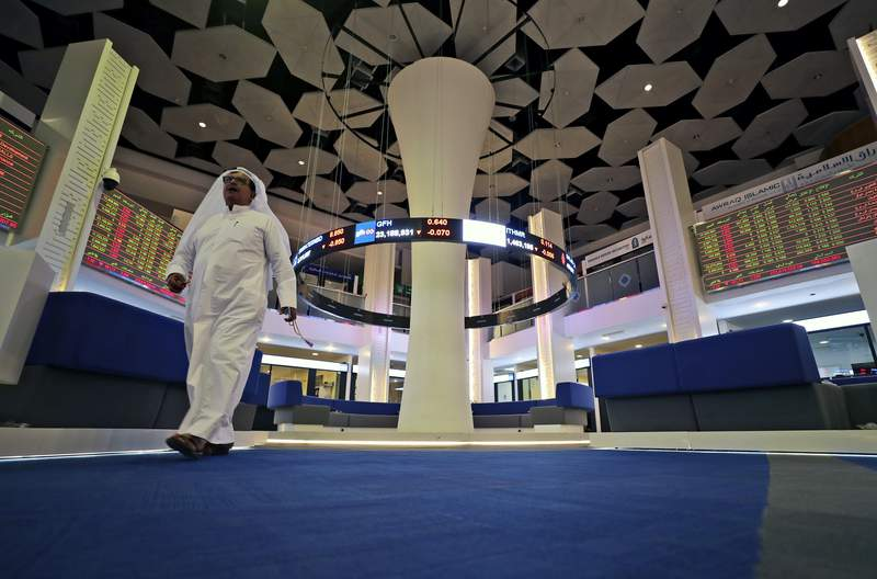 """A trader walks at the Dubai Financial Market in Dubai, United Arab Emirates, Thursday, March 12, 2020. Regional stock markets were down, reflecting investor concerns and nerves felt globally as oil prices plunge and tourism revenue is eroded by the virus. The World Health Organization on Wednesday officially designated the outbreak a """"pandemic."""" (AP Photo/Kamran Jebreili)"""