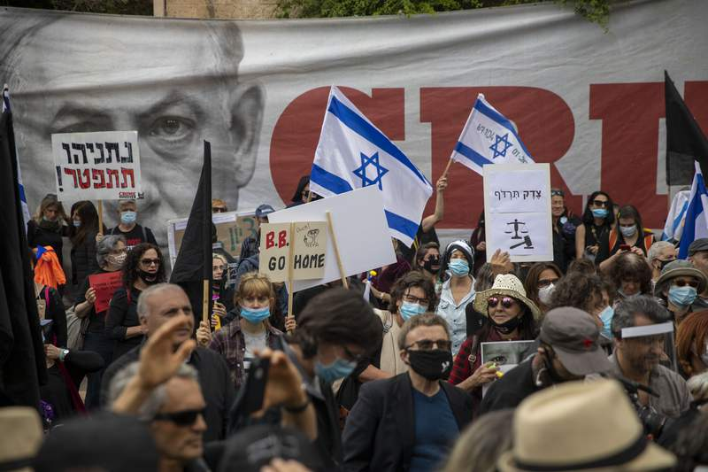 """Protesters against Israel's Prime Minister Benjamin Netanyahu wave flags and banners outside his residence in Jerusalem, Sunday, May 24, 2020. Hundreds of protesters calling him the """"crime minister"""" demonstrated outside his official residence, while hundreds of supporters, including leading members of his Likud party, rallied in support of him at the courthouse. Netanyahu faces charges of fraud, breach of trust, and accepting bribes in a series of corruption cases. The signs say """"Netanyahu resign,"""" and """"Justice shall you pursue."""" (AP Photo/Ariel Schalit)"""