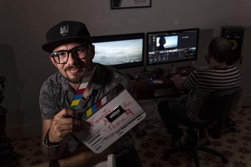 Carlos Gomez, 35, owner of the audiovisual production company Wajiros Films, poses for a photo at his company's editing room in Havana, Cuba, Thursday, Sept. 2, 2021. Most sorts of private businesses have been banned for more than 50 years, but now a new legal system takes effect on Sept. 20 that could greatly expand the scope of private businesses like Gomezs, and crucially give them greater legal certainty in efforts to help an economy in crisis. (AP Photo/Ramon Espinosa)