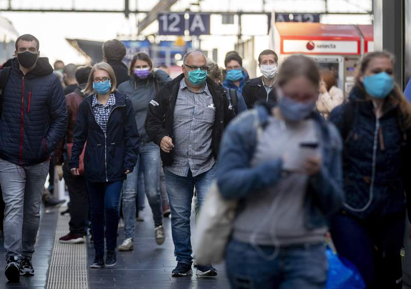 FILE - In this April 27, 2020, file photo, passengers wearing face masks arrive in the main train station in Frankfurt, Germany. Germany launched a coronavirus tracing app Tuesday, June 16, 2020, that officials say is so secure even government ministers can use it. Smartphone apps have been touted as a high-tech tool in the effort to track down potential COVID-19 infections. But governments in privacy-conscious Europe have run into legal and cultural hurdles trying to reconcile the need for effective tracing with the continents strict data privacy standards. (AP Photo/Michael Probst, File)