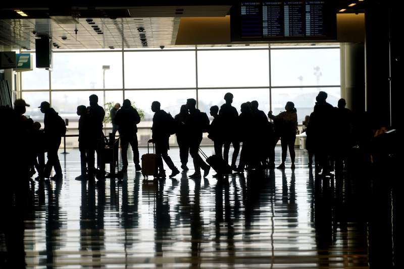 Travelers walk through the Salt Lake City International Airport Wednesday, March 17, 2021, in Salt Lake City.  Airlines and others in the travel industry are throwing their support behind vaccine passports to boost pandemic-depressed travel, and authorities in Europe could embrace the idea quickly enough for the peak summer vacation season.   (AP Photo/Rick Bowmer)