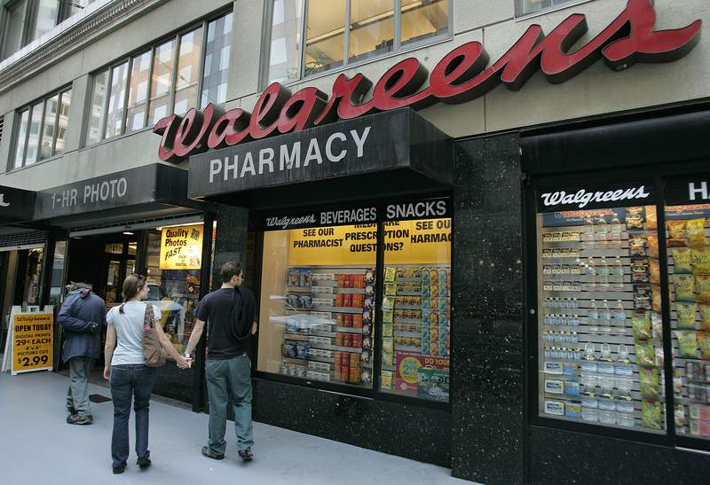 FILE - In this June 26, 2006 file photo, window shoppers look at a Walgreens storefront in San Francisco. Walgreens says it will close five more stores in San Francisco next month because of organized retail theft. The drugstore chain has closed at least 10 stores in the city since the start of 2019. (AP Photo/Ben Margot, File)